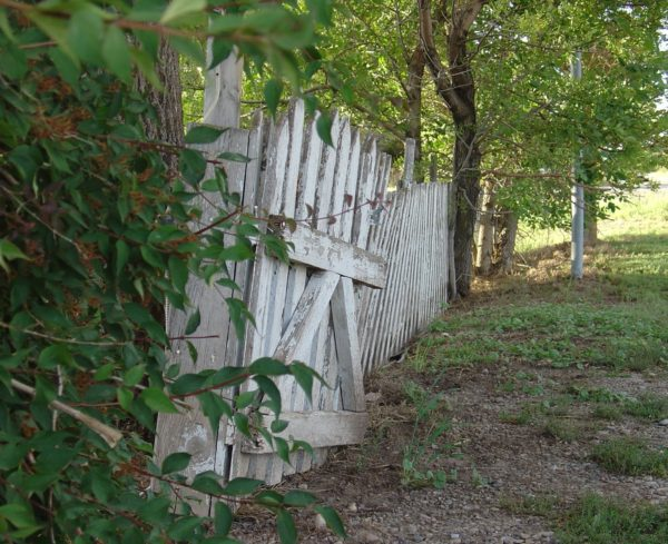 White fence in dire need of repair