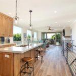 Living room of modern loft with wood floors, ample light and colorful kitchen backsplash