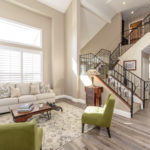light and bright living room with vaulted ceiling and wrought iron staircase