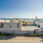 Newport Beach duplex with ocean and sand in the background and bike rider in front